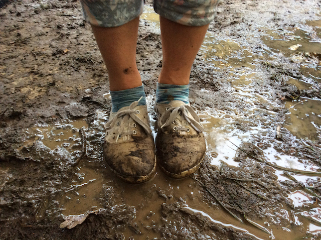 Very muddy dancing shoes standing in a muddy puddle